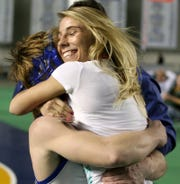 Camie Yeik congratulates her brother and teammate, Branden, after he won a state championship at Mat Classic in 2008. Camie Yeik placed sixth in the 103-pound weight division and is the last girl to win a medal in the boys tournament.