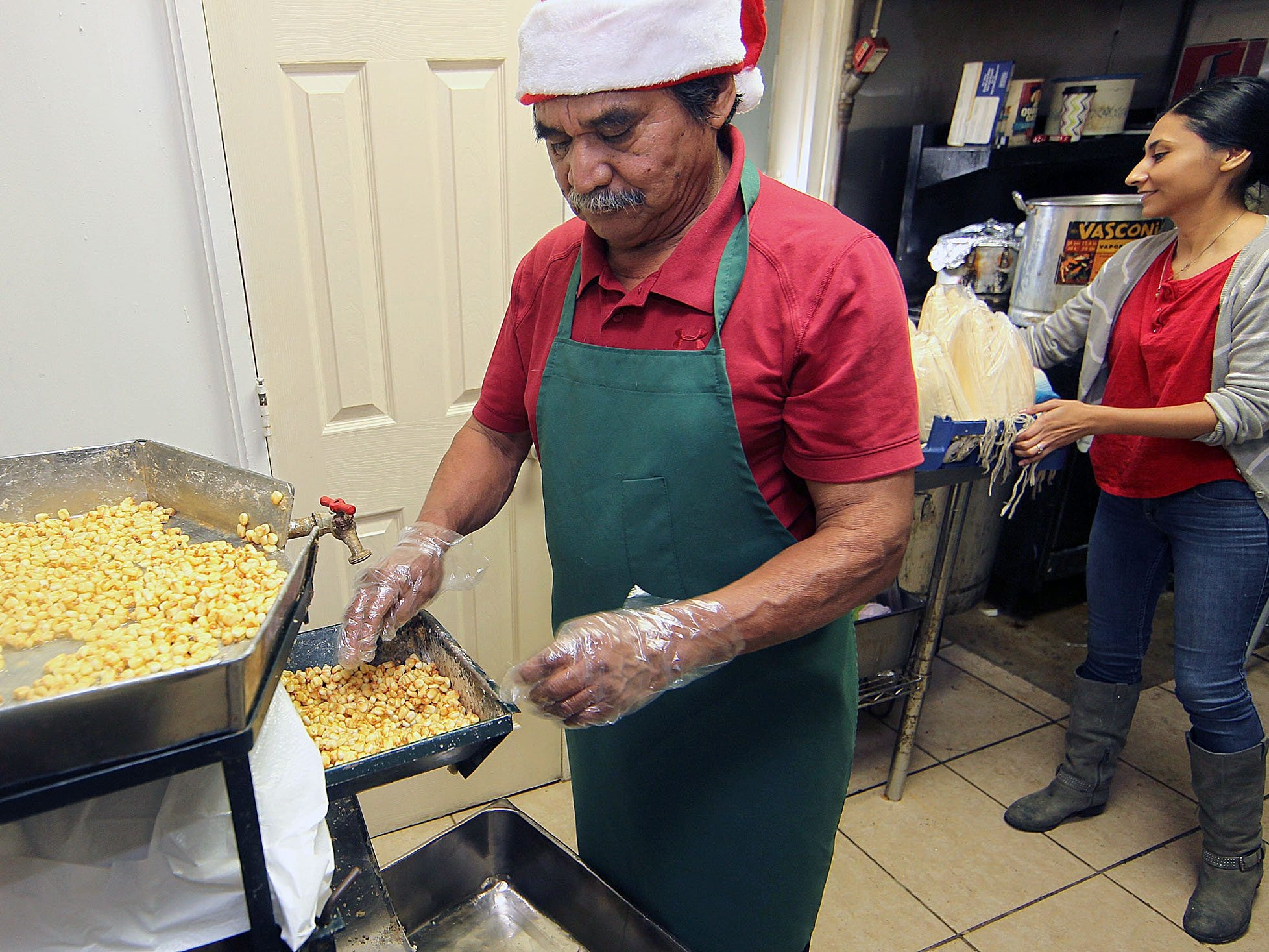 Jose Huerta who runs Huerta's Tamales with his wife, Maria, grinds corn in the back room of their shop on S. Staples Street as they try to keep up with the holiday order. The shop will close on Dec. 31, 2018.