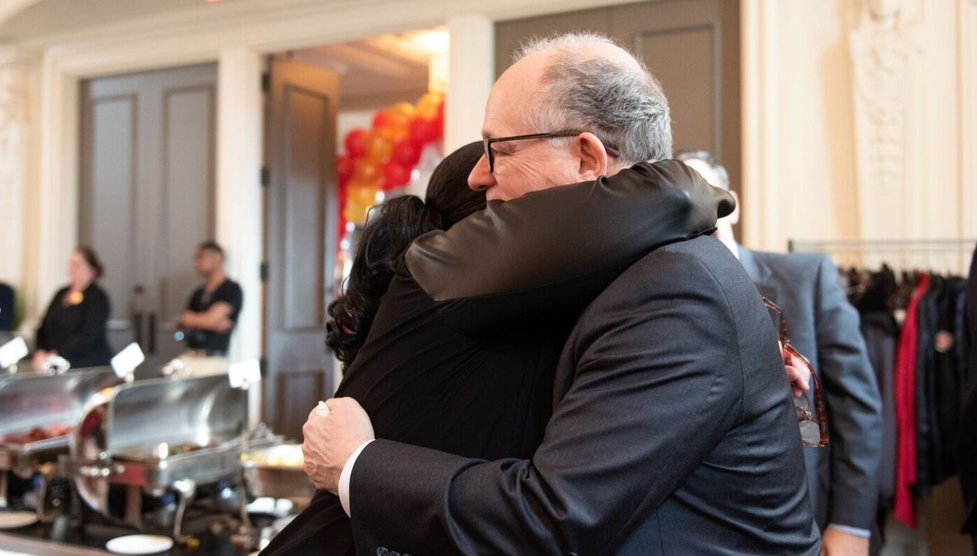Mark Baiada, founder of Bayada Home Health Care, shares a hug with an employee at a luncheon in Philadelphia Tuesday.