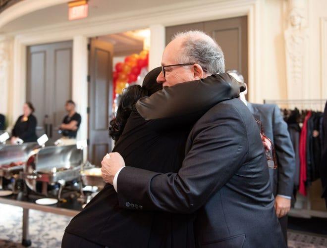 Mark Baiada, founder of Bayada Home Health Care, shares a hug with an employee at a luncheon in Philadelphia Tuesday.