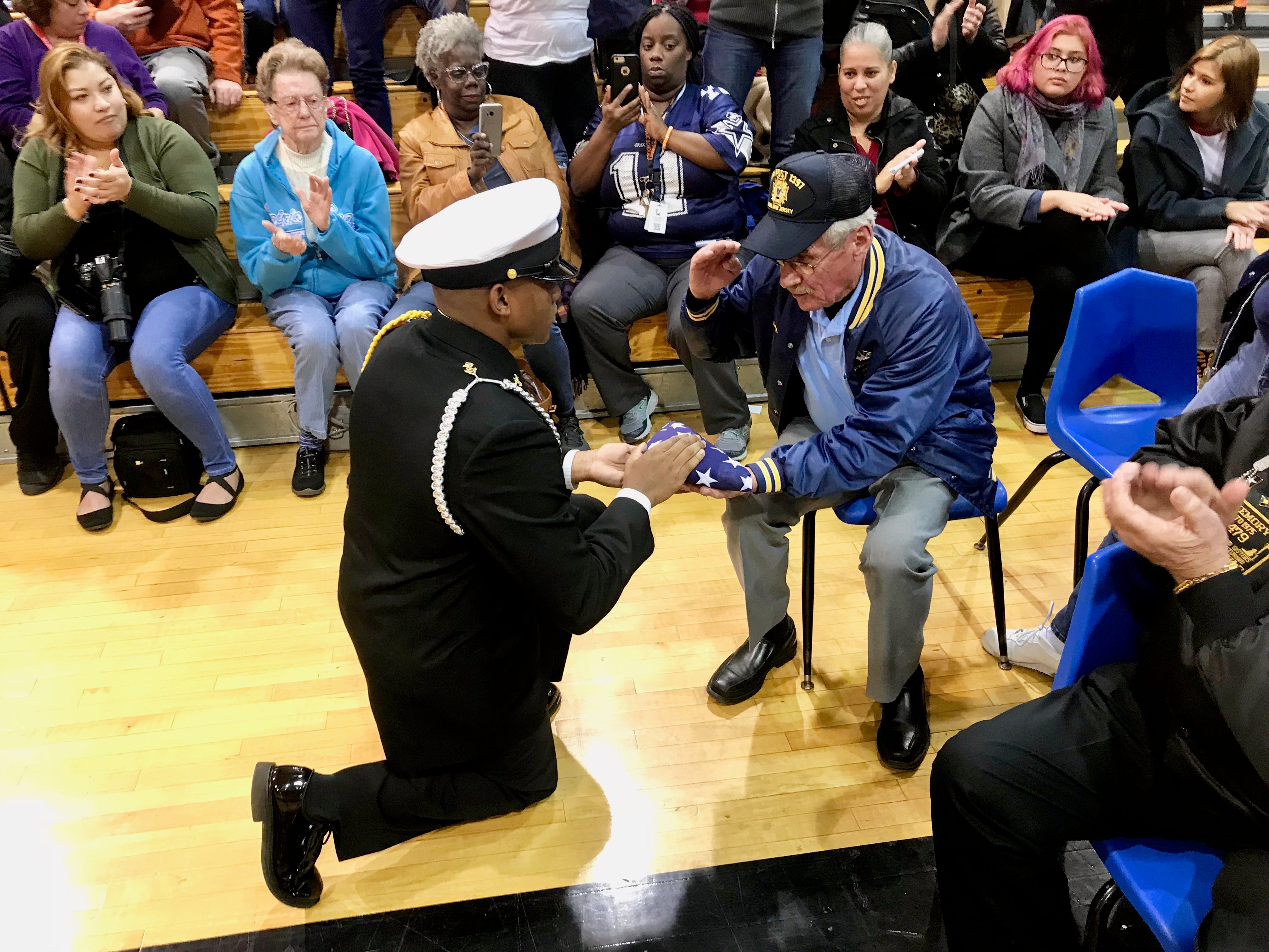 NJROTC1: Dennis Costello, commander of the Linden John Russell Wheeler VFW Post 1397, salutes Cadet Master Chief Petty Officer Maurice Faulk after being given a flag during the Old Glory Presentation at the Linden NJROTC Veterans Day ceremony.