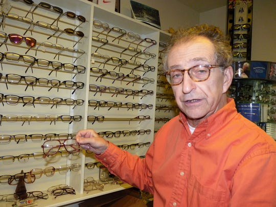David Weininger in front of a wall of glasses at his New Brunswick optometry office.
