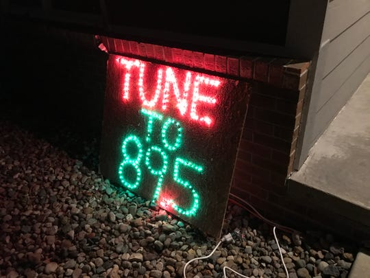 A sign outside the Davenport family's Ankeny home encourages people watching the lights to tune their radios to 89.5 FM, where they can hear the music for their timed light display.