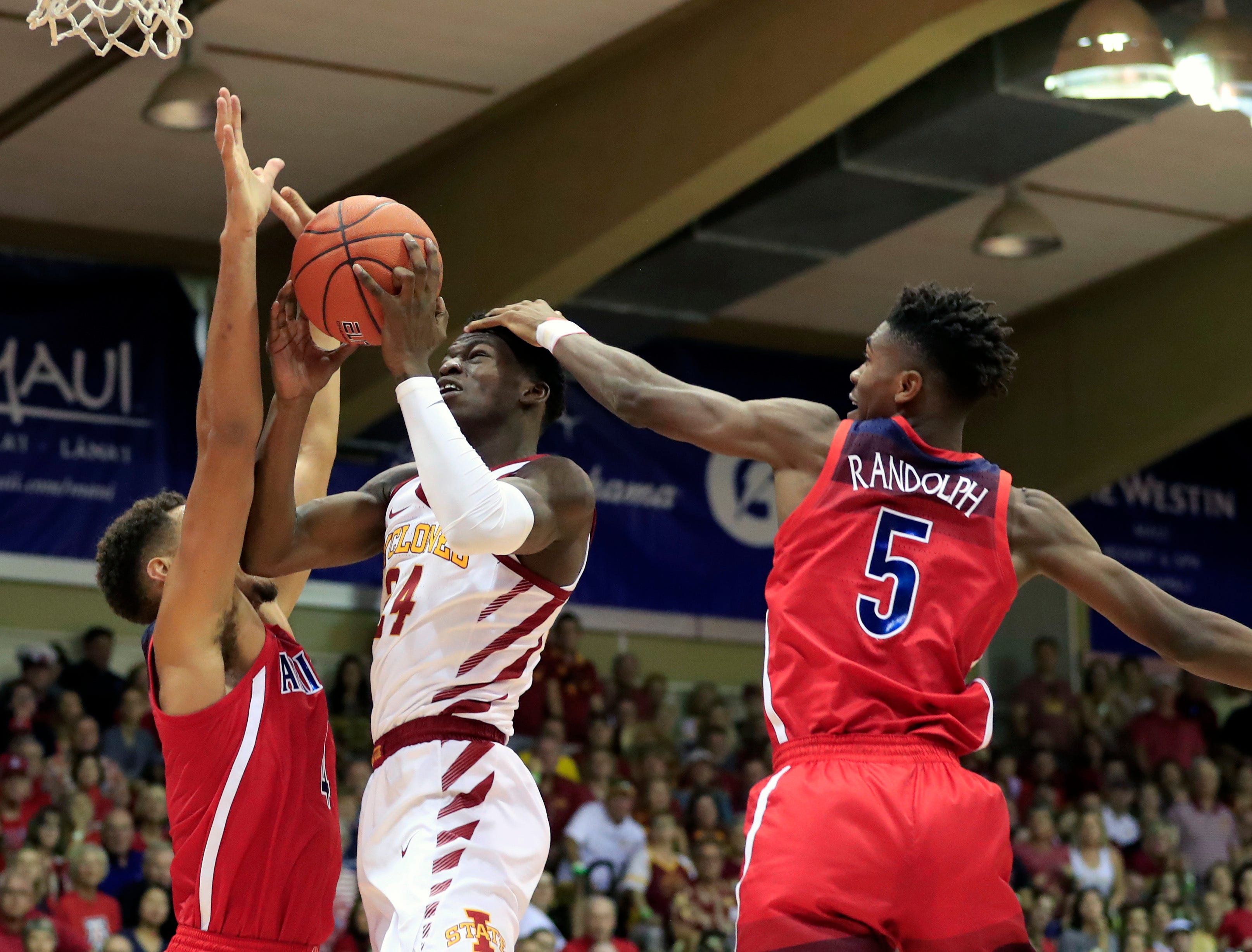 Iowa State guard Terrence Lewis (24) goes between Arizona center Chase Jeter (4) and guard Brandon Randolph (5) during the first half of an NCAA college basketball game at the Maui Invitational, Monday, Nov. 19, 2018, in Lahaina, Hawaii.