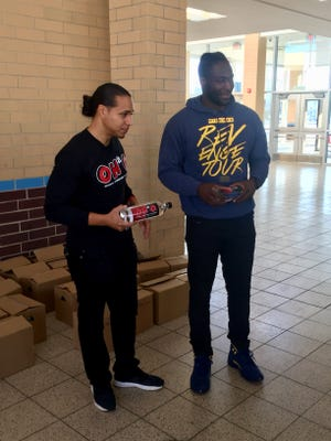 Former college football rivals, Donnie Evege of Ohio State and Devin Gardner of Michigan, work together to help fix the water crisis at Mumford High School in Detroit by passing out bottle water.