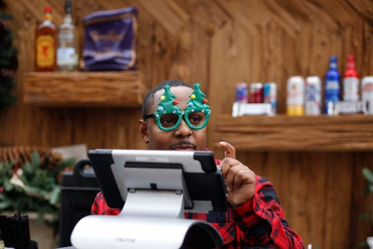 Bartender Tyron Foster, of Detroit, takes an order while wearing festive glasses from inside Cadillac Lodge on Sunday, Nov. 18, 2018 in Cadillac Square in Detroit.