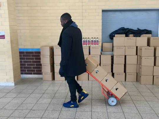 Devin Gardner, a former Michigan quarterback, helps deliver bottled water to Mumford High School.