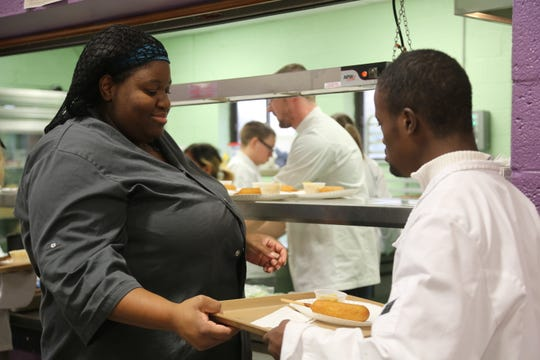 Chef Jasmine Jones serves lunch to Dyniel Union, a student at Rising Stars Academy, a charter school in Center Line that teaches culinary and life skills to special needs students.