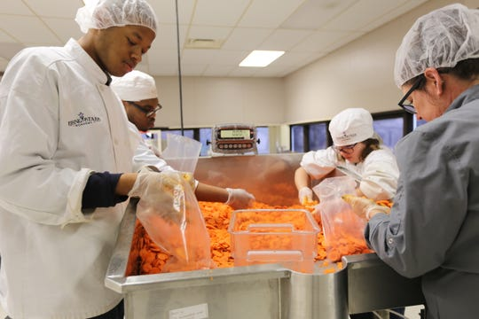 From left: Students Kyle Smith, James Hunt, Sarah Dzielski and Chef Lisa Woodward process carrots for restaurants at Rising Stars in Center Line.