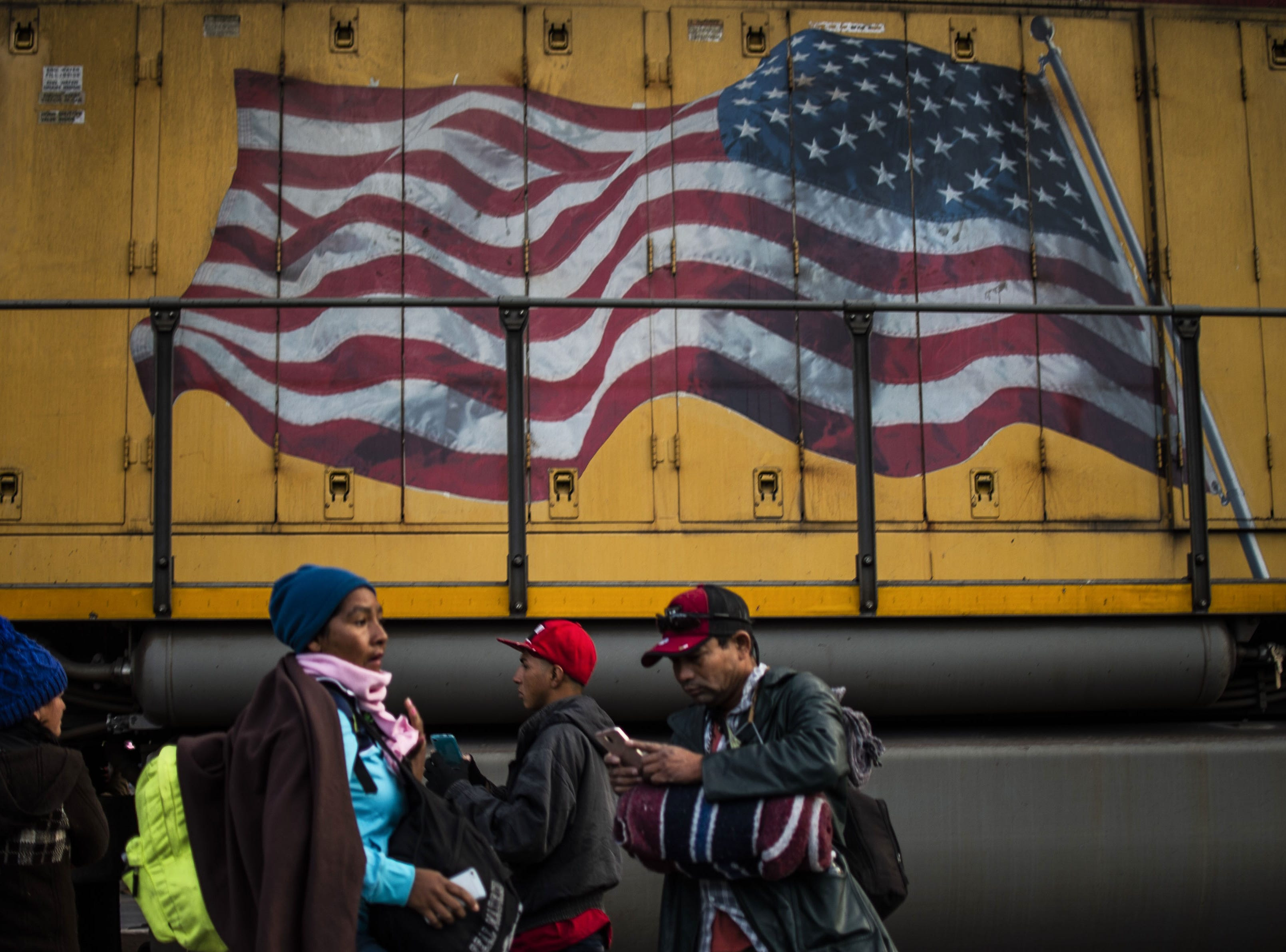 Central American migrants -mostly Hondurans- moving towards the United States in hopes of a better life, are pictured near a train painted with the US national flag, in the Mexican border city of Mexicali, Baja California state on their way to Tijuana, Mexico, on November 20, 2018. - Some 800 Central American migrants trekking across Mexico in a caravan aiming at the US, left Mexicali on Tuesday morning heading to Tijuana, where an increasingly reinforced border and growing hostility await them.