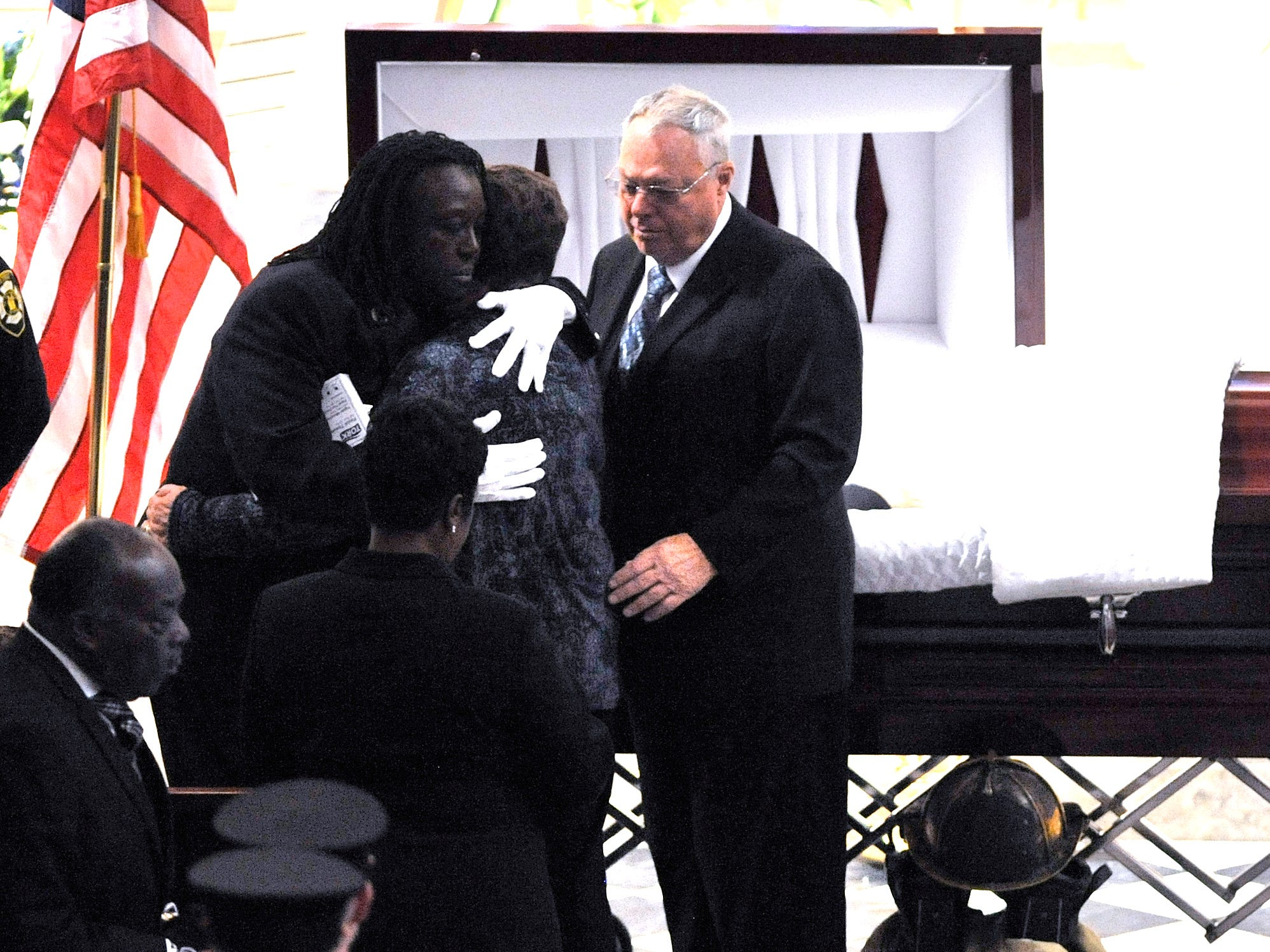 Loved ones embrace at the casket before firefighters file into the church.