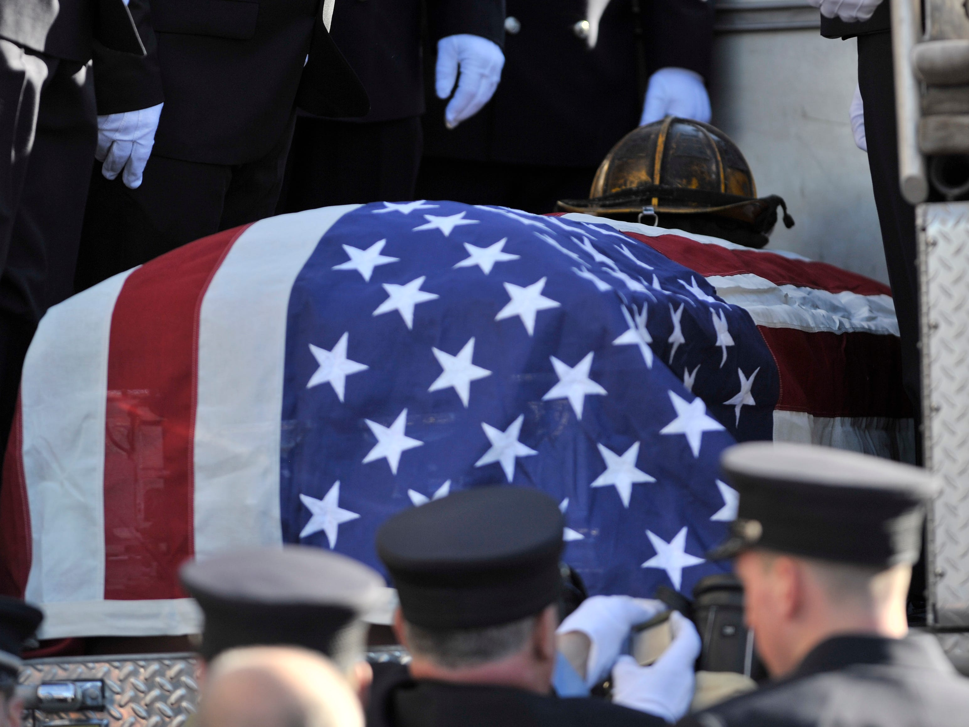 The helmet of the fallen Detroit firefighter rests on his casket before this engine proceeds to the cemetery.