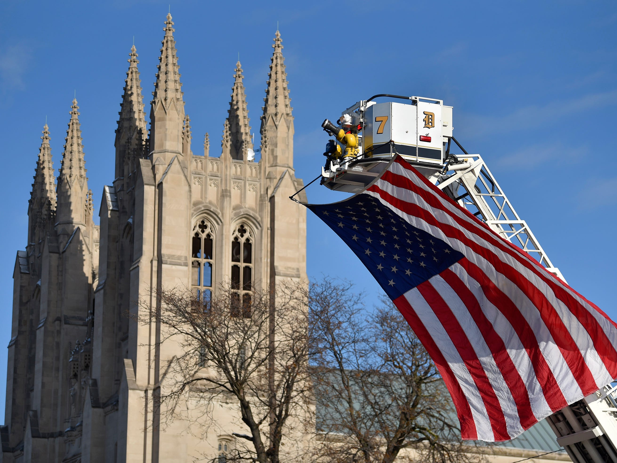 The U.S. flag flies from the platform of Detroit Fire Department Ladder 7 as hundreds of firefighters, family members and friends pay their respects to fallen Detroit firefighter Michael Lubig in a service at the Cathedral of the Most Blessed Sacrament in Detroit, Tuesday, Nov. 20, 2018.