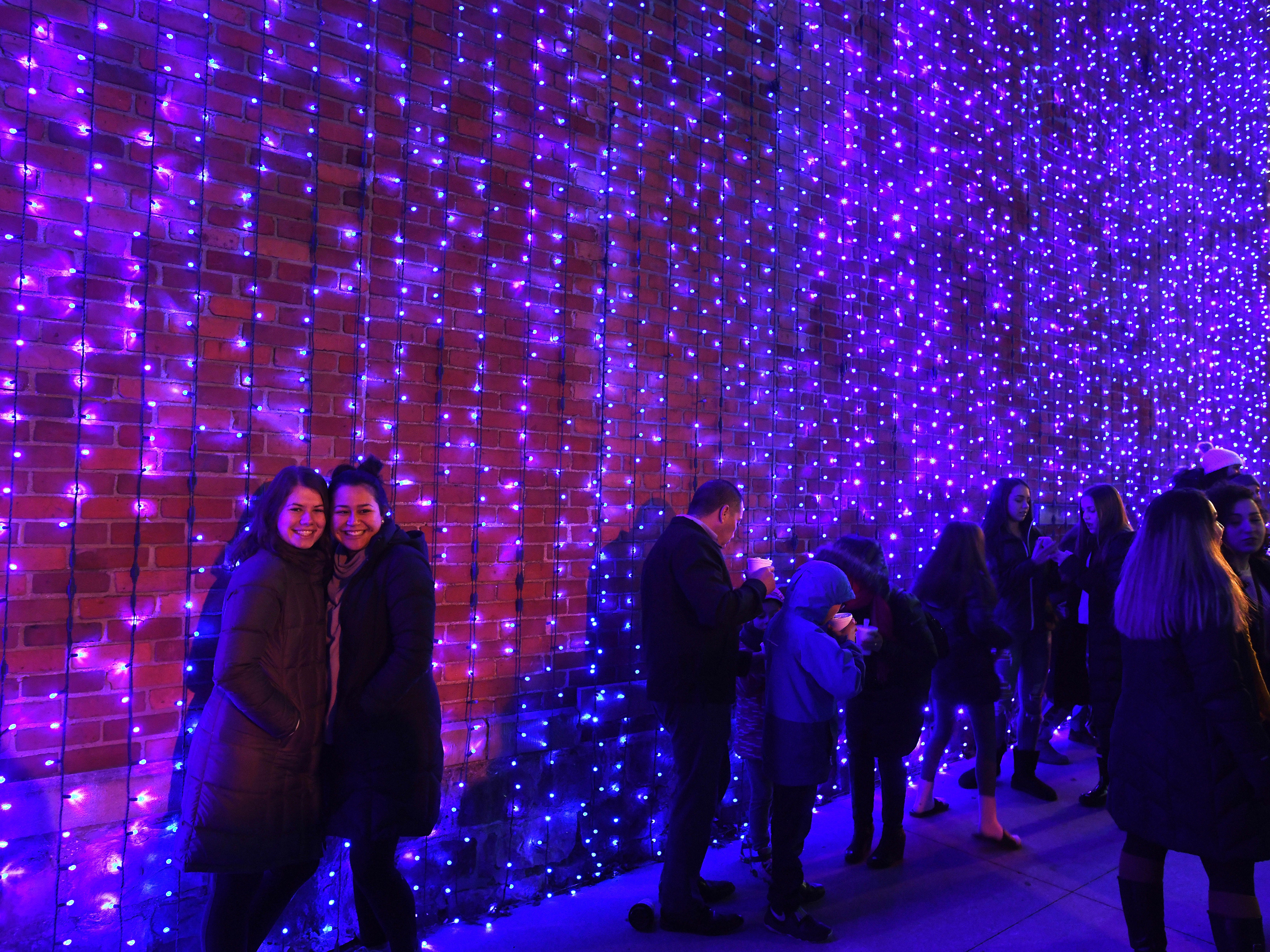 Peggy Laci and Anna Nickel pose for a picture against a wall of lights at The Big, Bright Light Show in downtown Rochester.