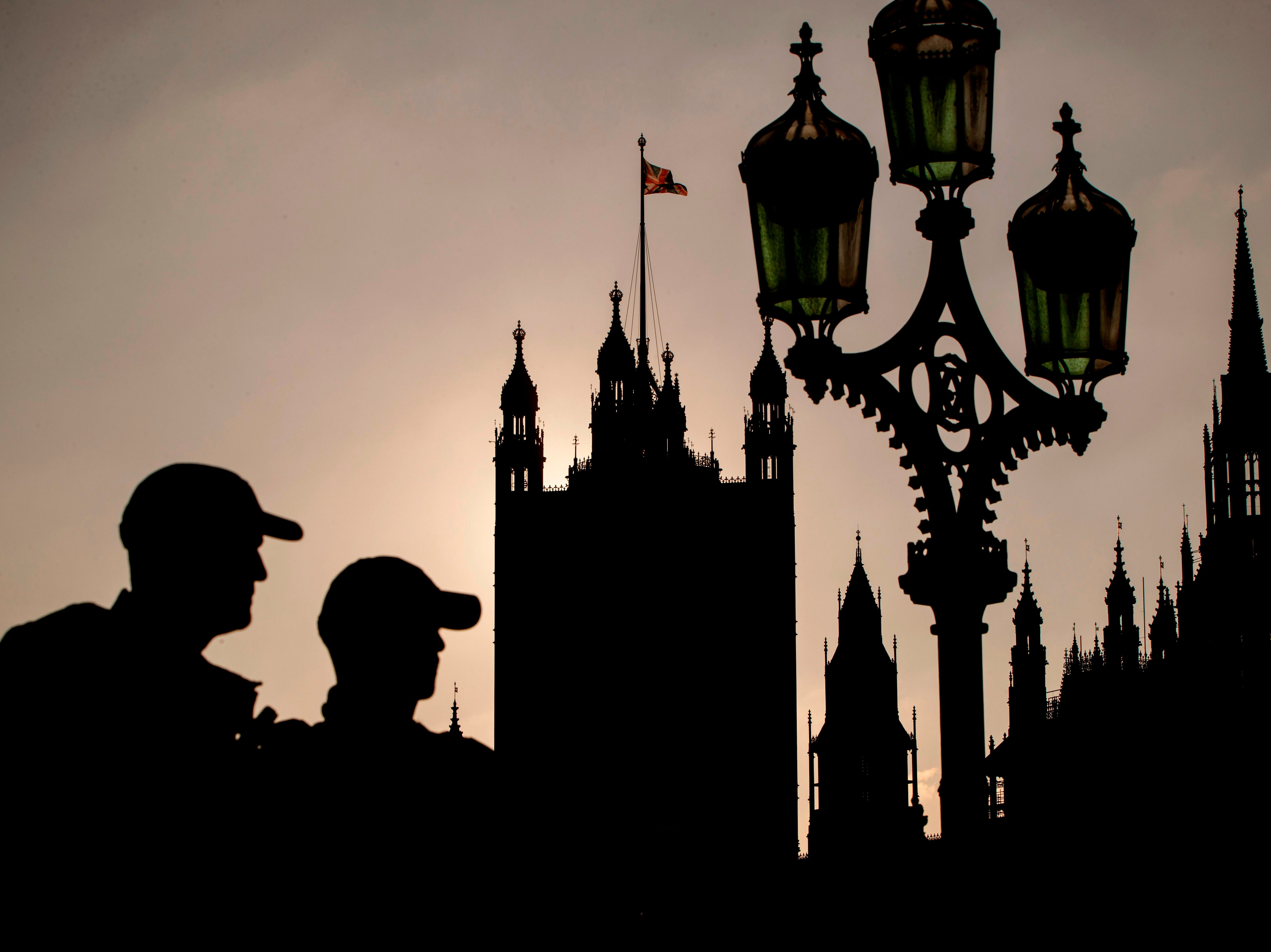 A Union flag flies from atop the Houses of Parliament as pedestrians walk across Westminster Bridge in London on November 17, 2018. - British Prime Minister Theresa May on Saturday told the plotters planning to overthrow her that their alternative Brexit plans would not resolve all their problems with her draft deal. May is fighting to salvage her proposed Brexit agreement -- and her job -- after a tumultuous week in which four ministers resigned, MPs slammed the proposal and members of her own party tried to oust her.