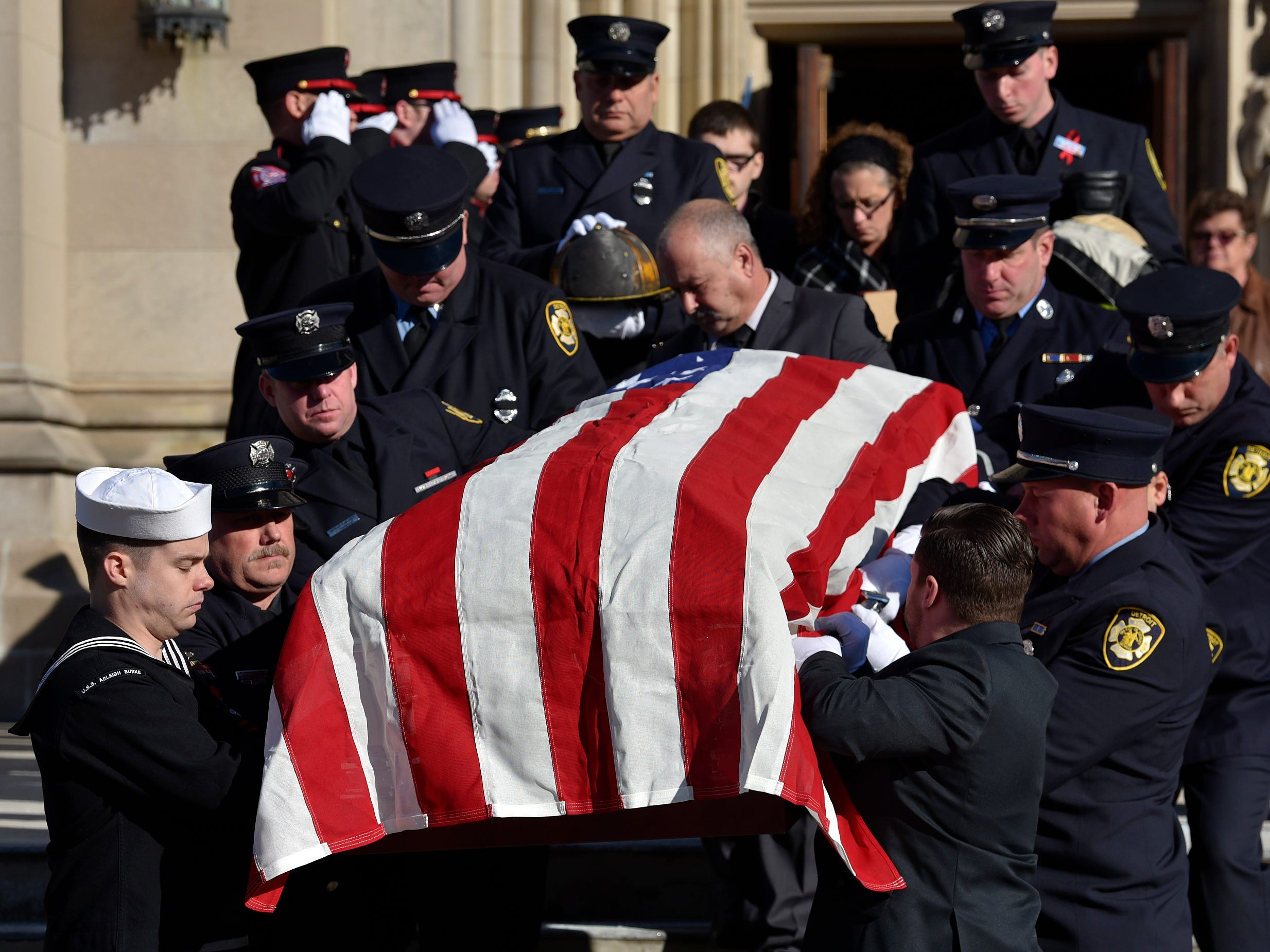 Pall bearers carry the casket of fallen Detroit firefighter Michael Lubig.