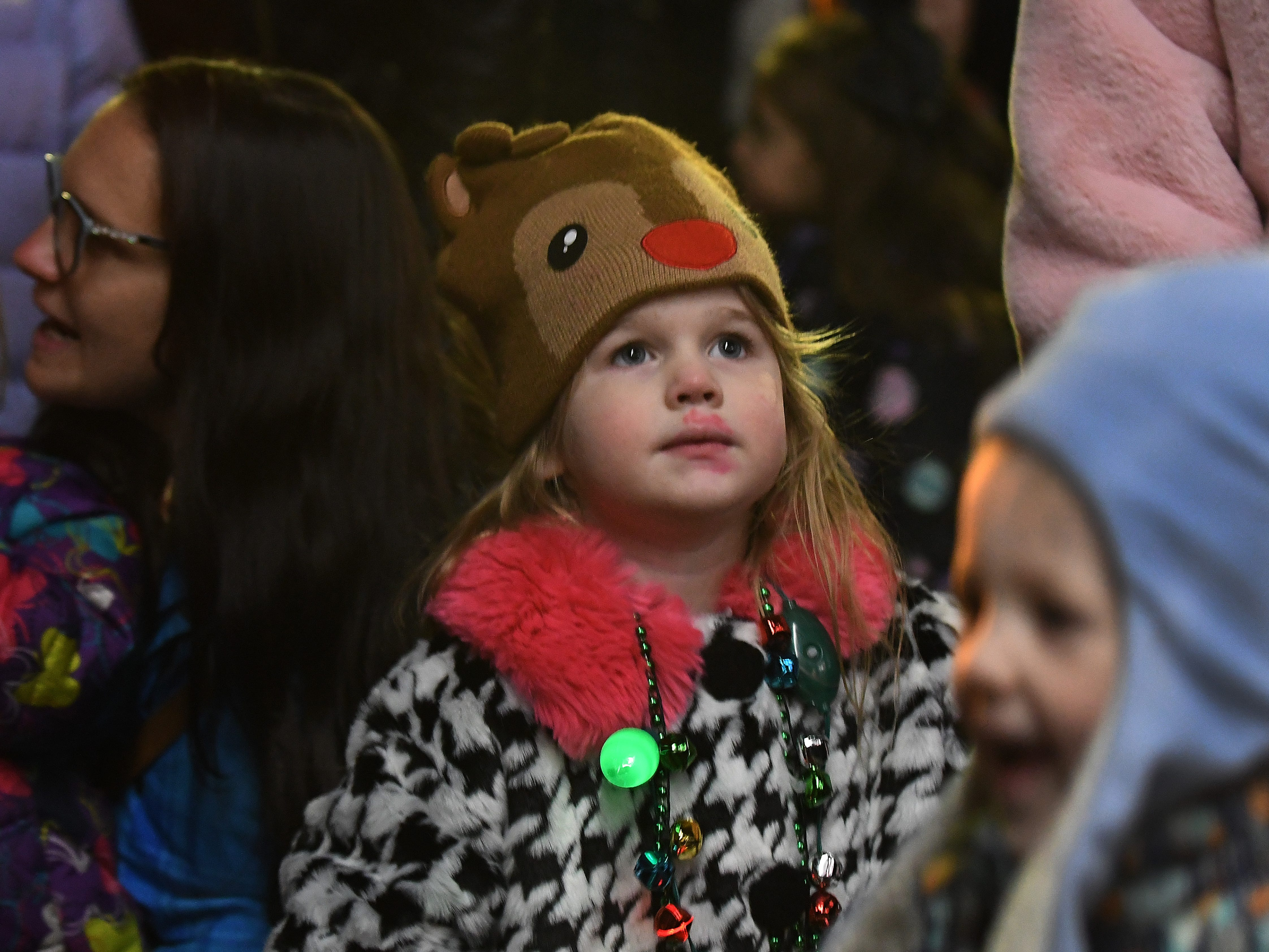 Ivy Savage, 3 listens to Christmas carols as she waits patiently for Santa Claus to arrive during the Big, Bright Light Show in downtown Rochester.