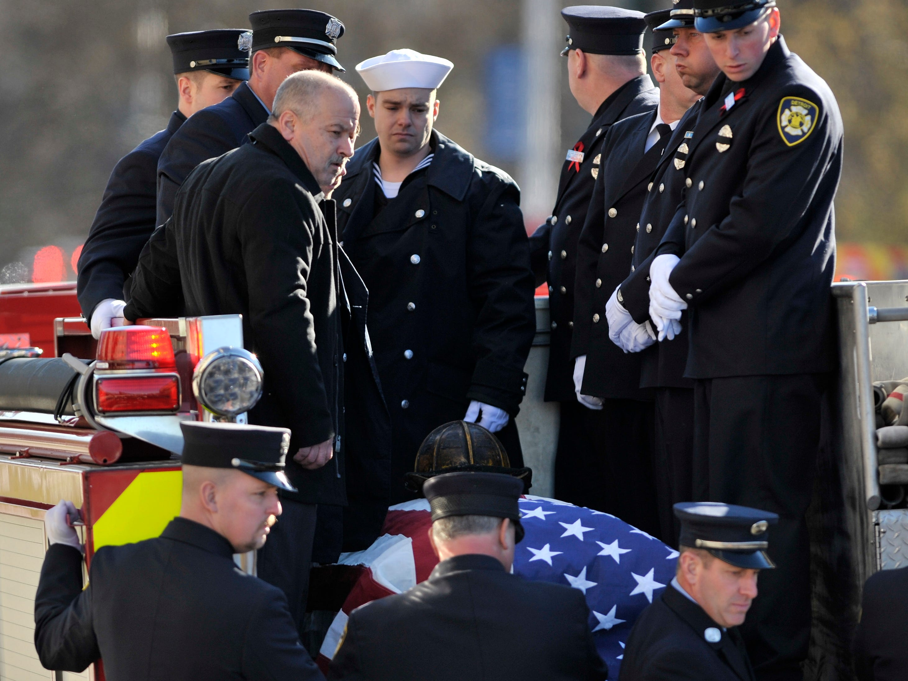 Pall bearers and others encircle the casket of fallen Detroit firefighter Michael Lubig before proceeding to the cemetery.