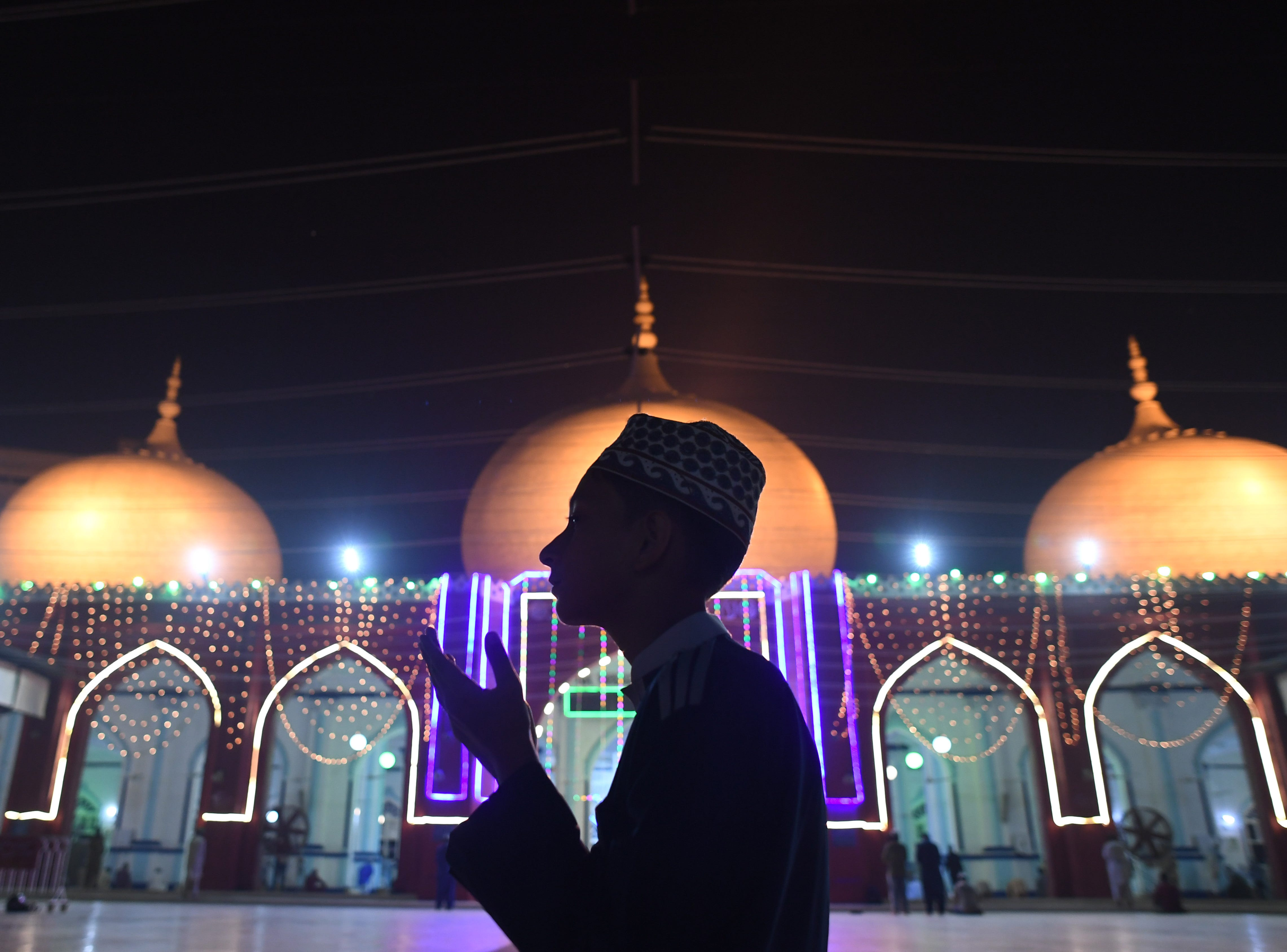 A Pakistani Muslim prays at an illuminated mosque in connection with Eid-e-Milad-un-Nabi, the birthday of Prophet Mohammad, in Karachi on November 20, 2018. - From sufis in Iraqi Kurdistan shaking their hair to rhythmic drumbeats, to Libyan children receiving toys and Egyptians swapping sweets -- Muslims across the world celebrated Prophet Mohammed's birthday on November 20. Several thousand kilometres (miles) away in Pakistan, mosques are elaborately illuminated with strings of light to celebrate, while in Morocco, the day typically sees the king grant widespread amnesties.