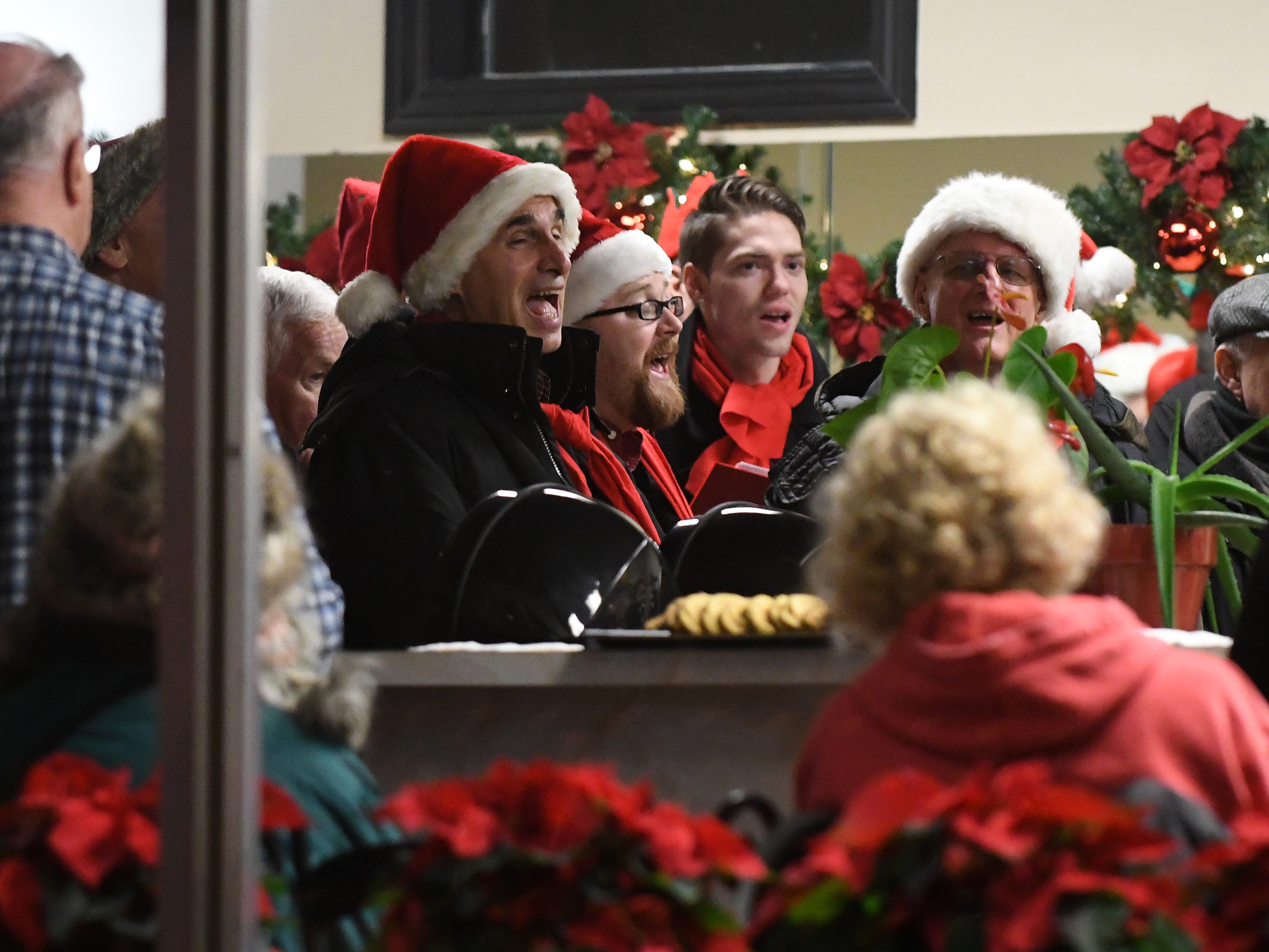 Christmas caroling inside the Goldfingers Salon off Main Street in downtown Rochester.