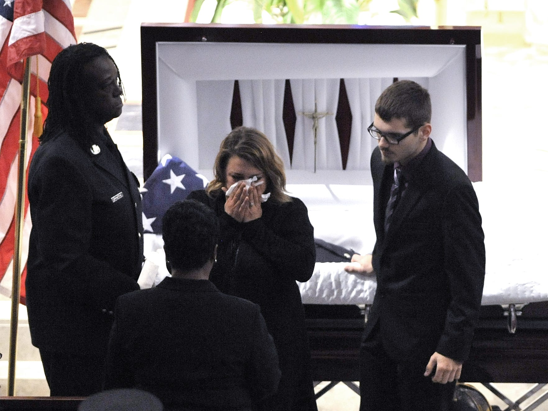 A loved one cries as she pays her respects before firefighters file into the church.