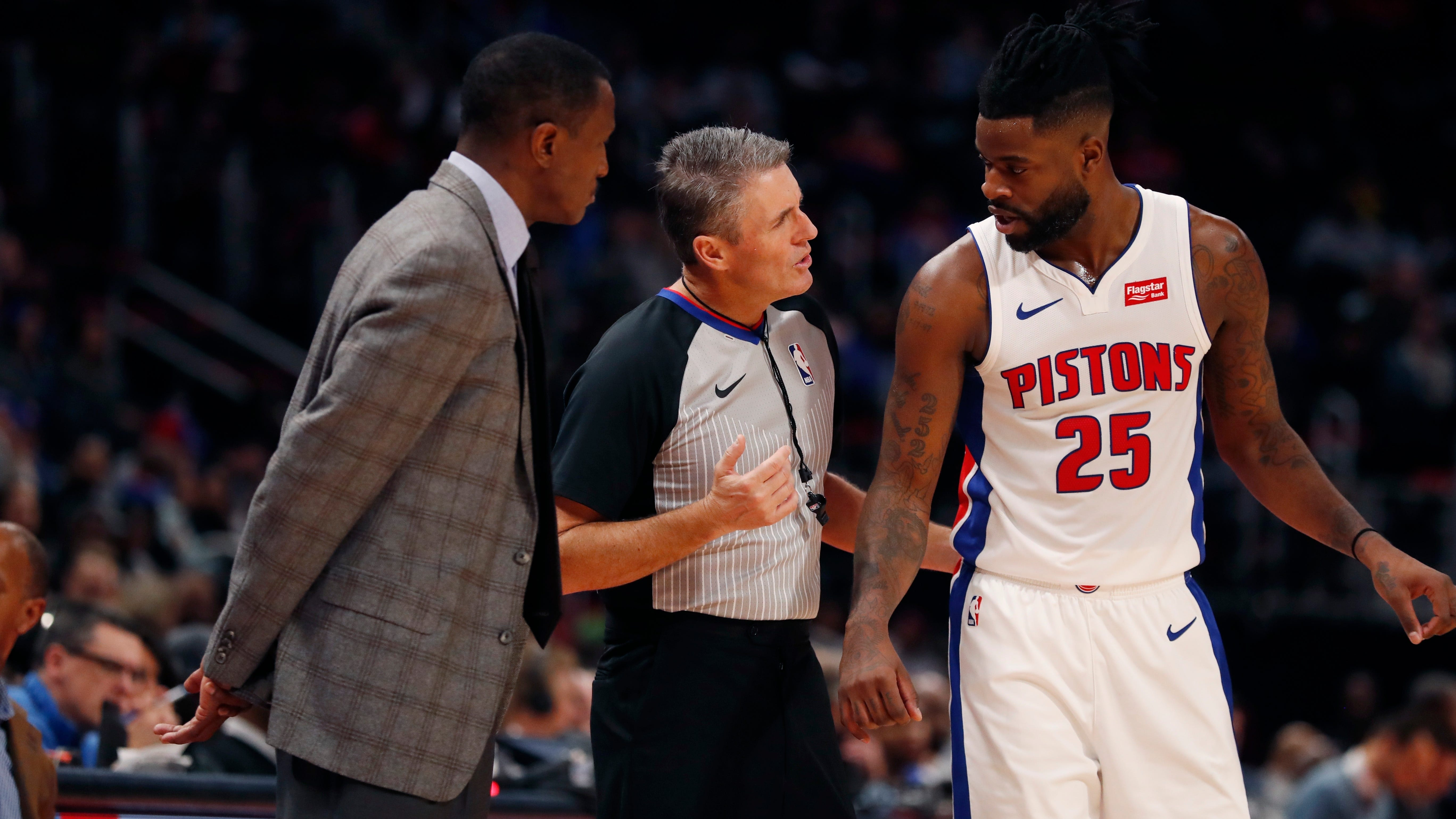Referee Scott Foster talks with Detroit Pistons head coach Dwane Casey and guard Reggie Bullock during the second half Monday night.