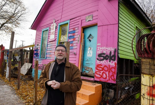 Tim Burke, 59, stands in front of his former home at 3647 Heidelberg Street in Detroit. Burke is an artist who, like his neighbor Tyree Guyton, uses a lot of found objects in his art.