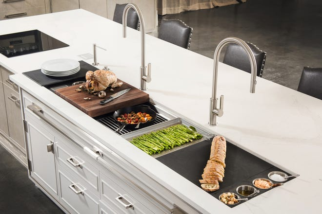 AT HOME for release NOVEMBER 2018 HOME TOUCH Caption 4: Modular workstations set over a large sink are getting people to think linearly when it comes to kitchen design. Cutting boards and racks are designed to fit on the ledge of the sink, while the cooktop is within reach of freshly prepared ingredients.