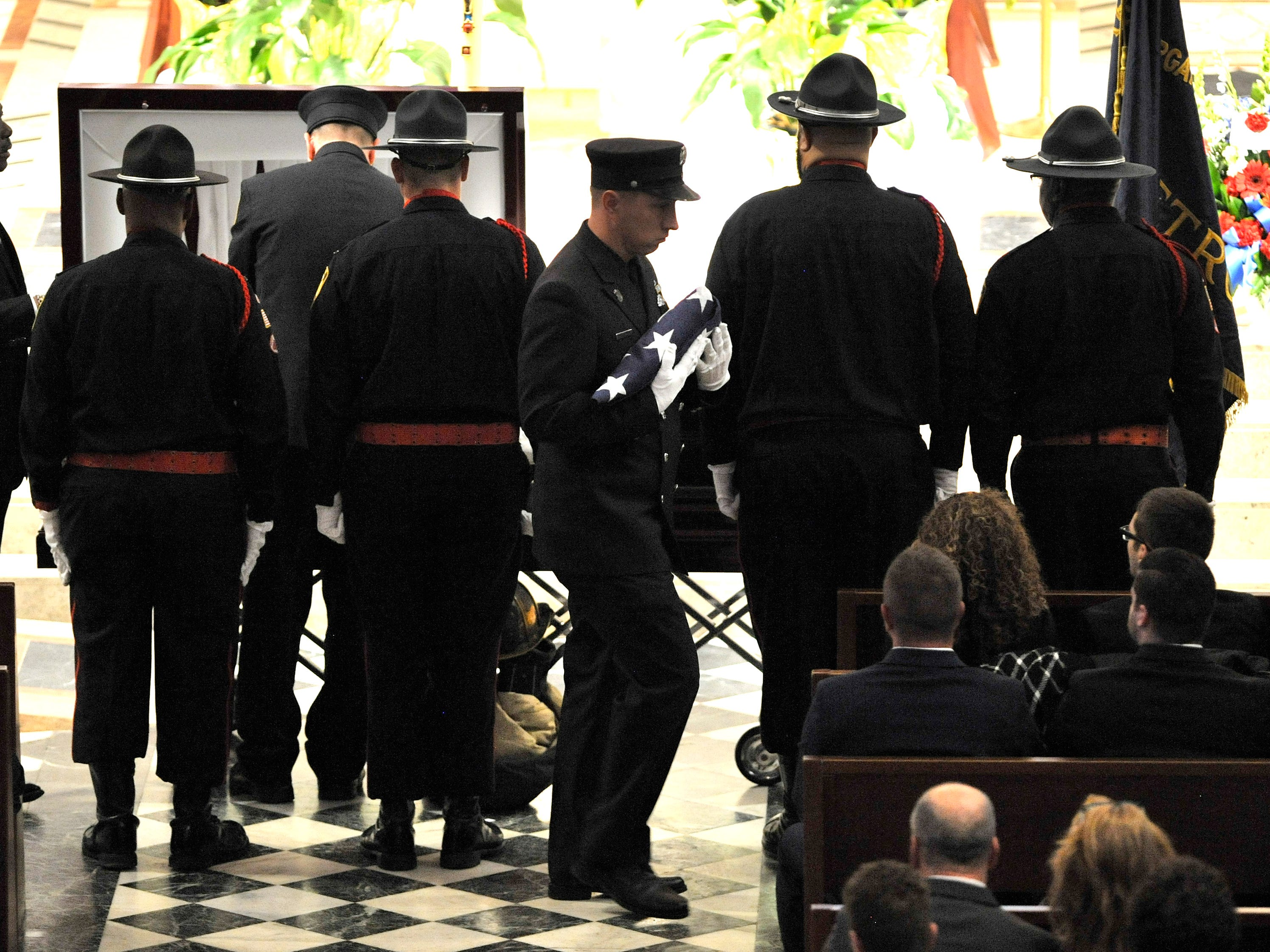A firefighter carries the U.S. flag to present it to a family member before the casket is closed.