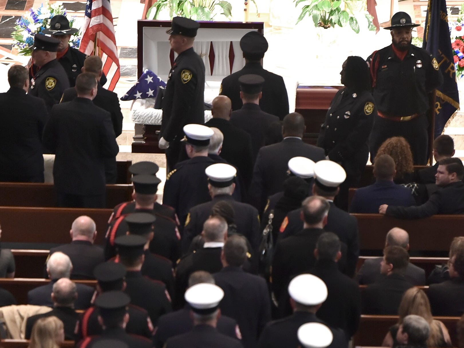 Fire department chiefs wearing white hats file into the church with rank-and-file firefighters at the beginning of the service.