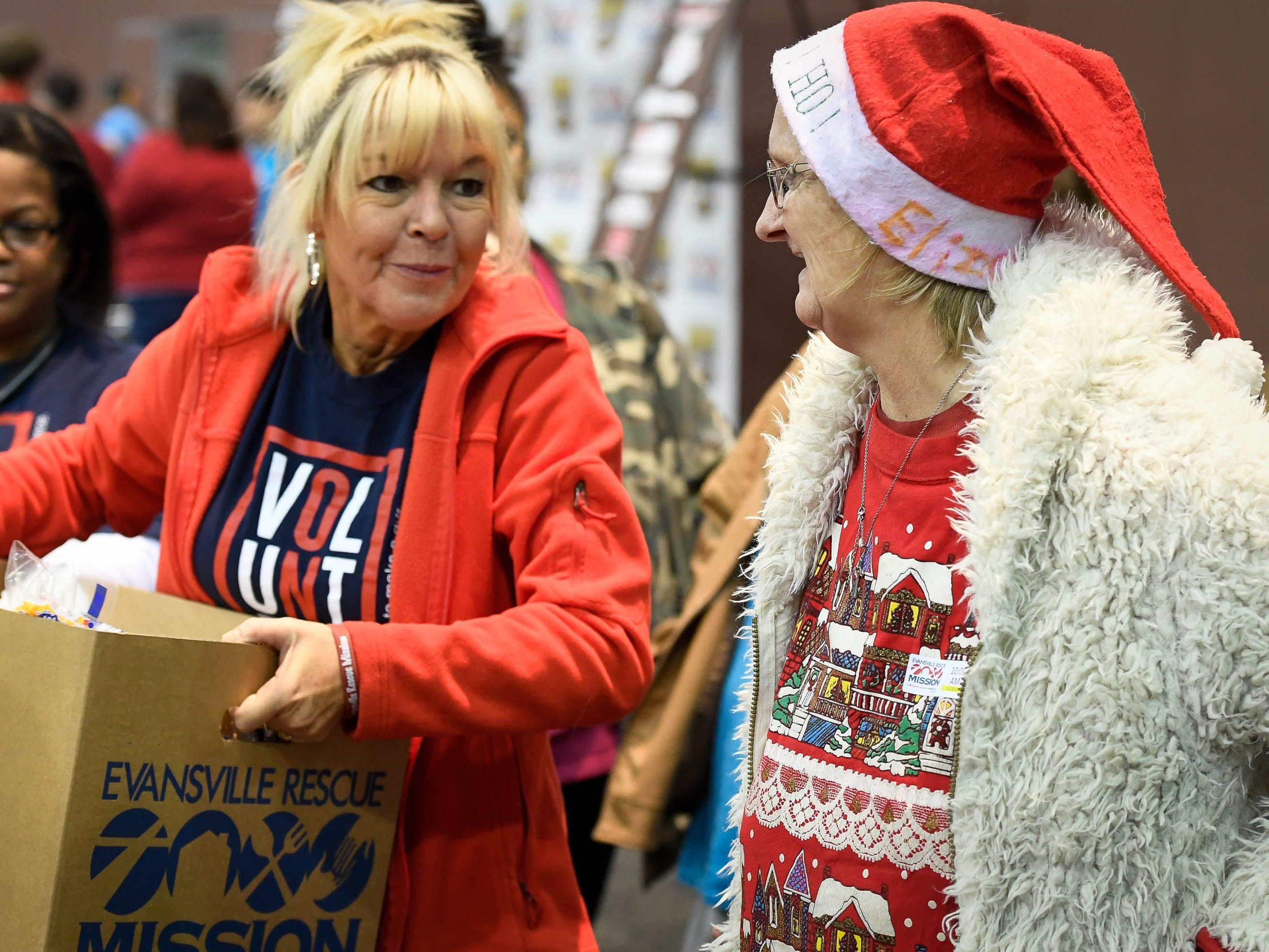 Volunteer Sarah Wooten, left, Mt. Vernon, helps Elizabeth Prange with her food box at the Evansville Rescue Mission's 96th annual Gobbler Gathering held at the Old National Events Plaza Tuesday, November 20, 2018.