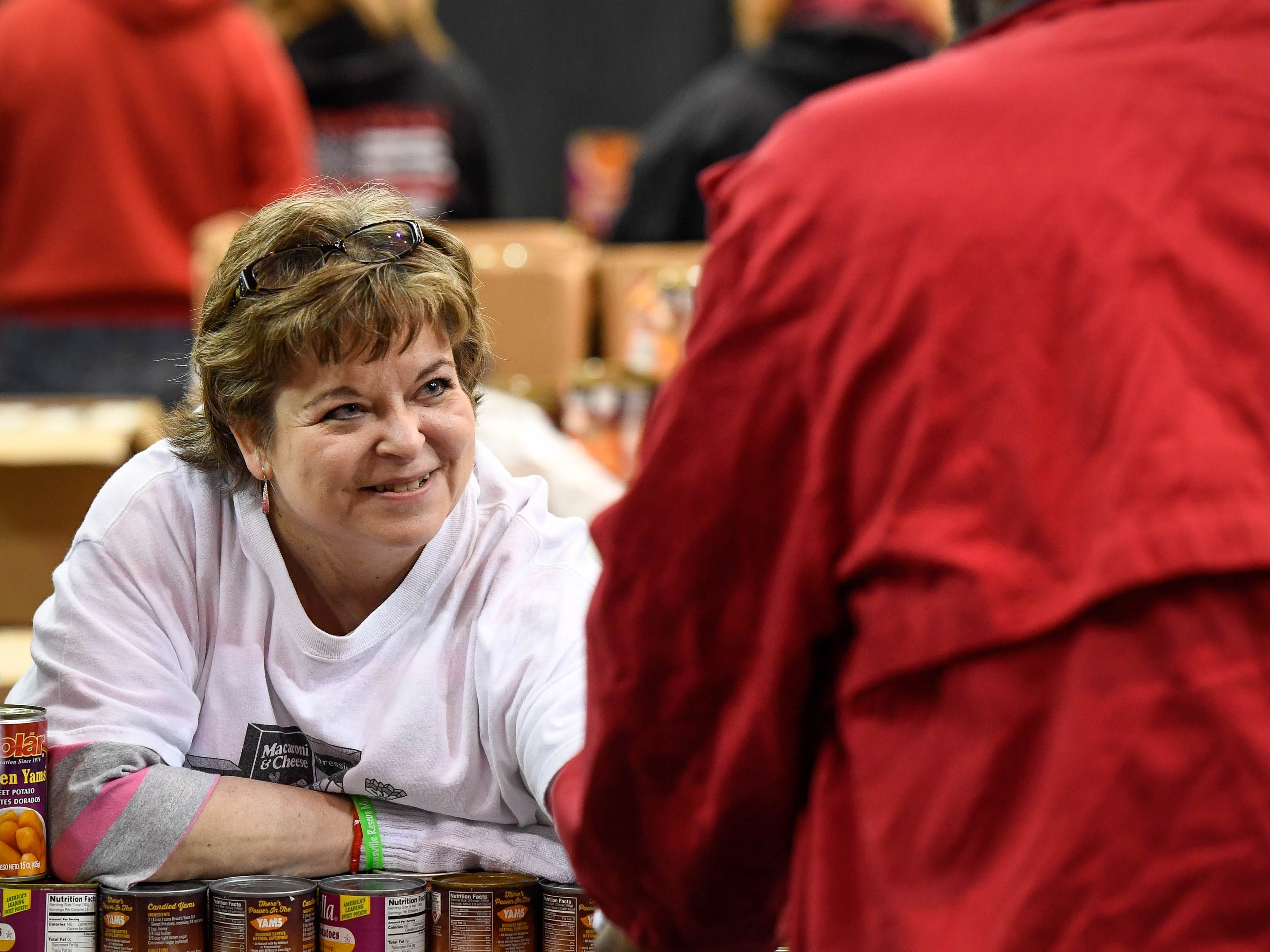 Volunteer Angie Ezell shakes hands with people passing through the food box line at the Evansville Rescue Mission's 96th annual Gobbler Gathering held at the Old National Events Plaza Tuesday, November 20, 2018.