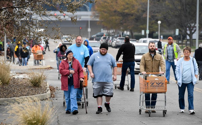 Volunteer helpers and families in need leave with food boxes at the Evansville Rescue Mission's 96th annual Gobbler Gathering held at the Old National Events Plaza Tuesday, November 20, 2018.