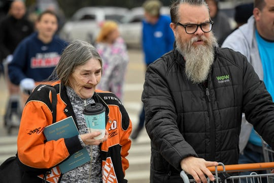 Using a shopping cart, Volunteer Jimmy DeTalente helps Mary Davis get her food box to her car at the Evansville Rescue Mission's 96th annual Gobbler Gathering held at the Old National Events Plaza Tuesday, November 20, 2018.