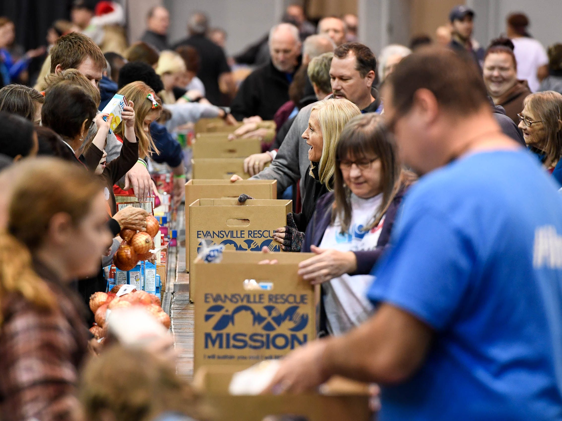 Volunteer helpers assist families in need fill food boxes at the Evansville Rescue Mission's 96th annual Gobbler Gathering held at the Old National Events Plaza Tuesday, November 20, 2018.