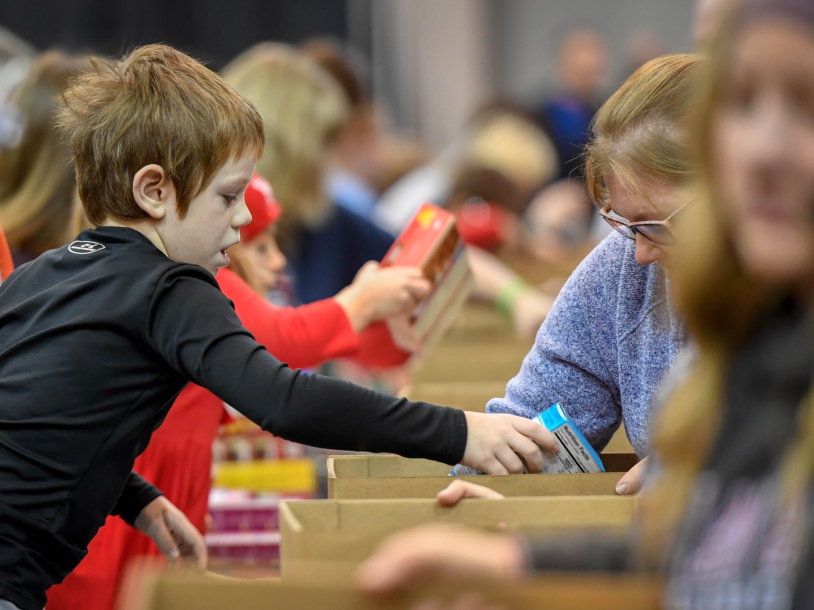 Doing his part, Carson Hetzel-Gaynor, 7 years-old, puts boxes of muffin mix into food boxes at the Evansville Rescue Mission's 96th annual Gobbler Gathering held at the Old National Events Plaza Tuesday, November 20, 2018.