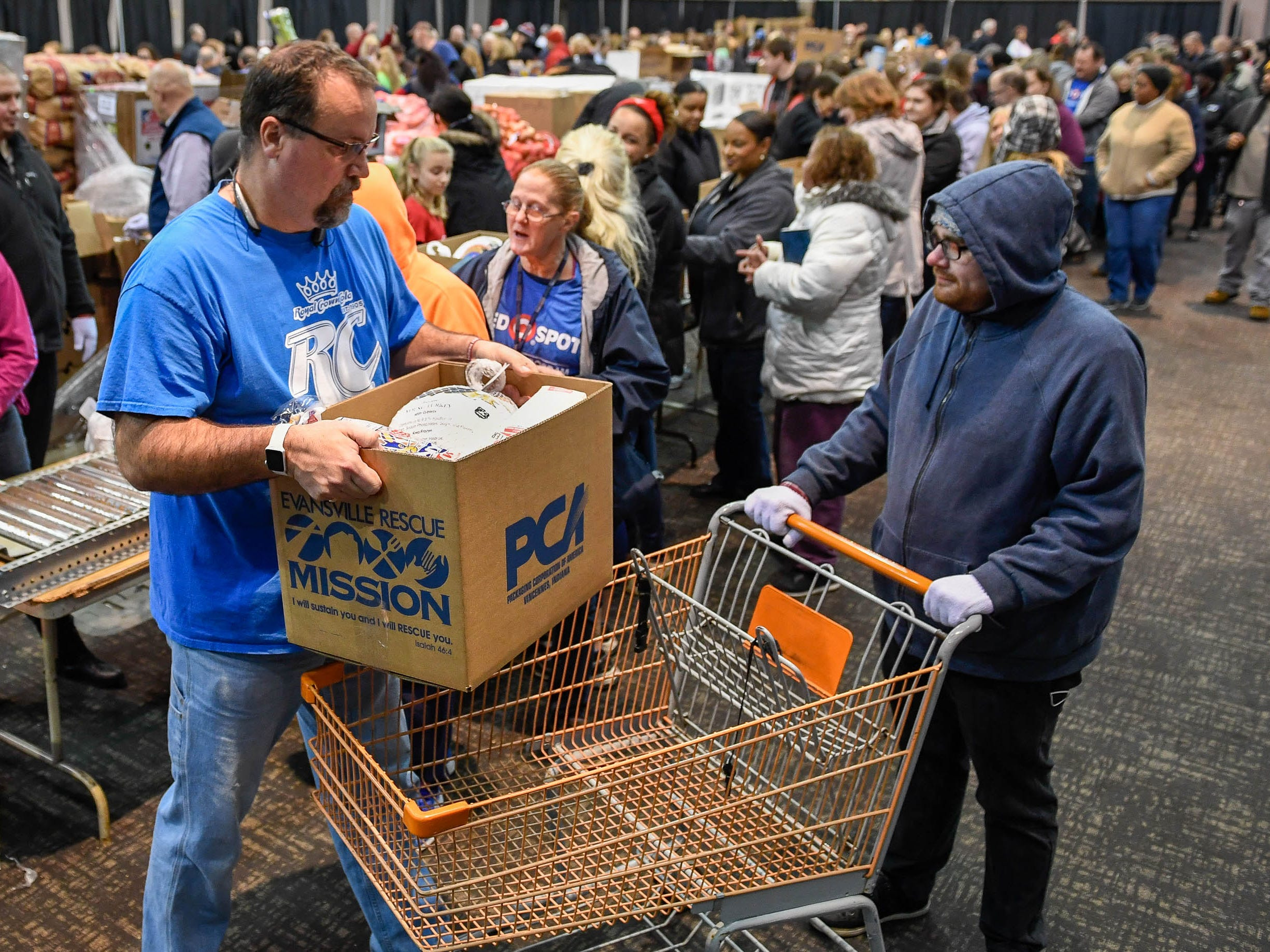 Volunteers Javan Anderson puts a loaded food box into a cart so Jaymes Harmon can take to the parking lot at the Evansville Rescue Mission's 96th annual Gobbler Gathering held at the Old National Events Plaza Tuesday, November 20, 2018.