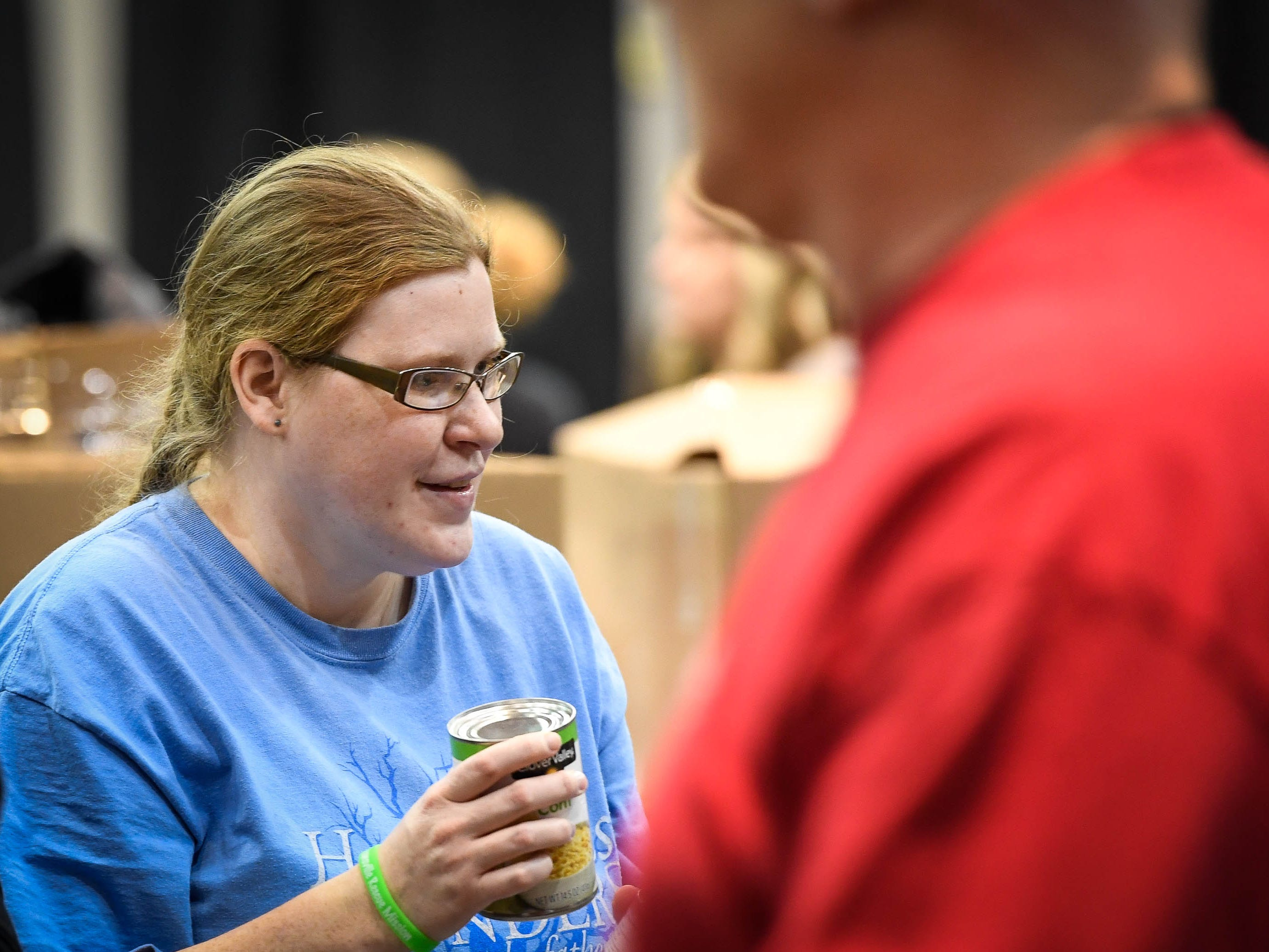 Volunteer Emily Oakley hands out canned vegetables at the Evansville Rescue Mission's 96th annual Gobbler Gathering held at the Old National Events Plaza Tuesday, November 20, 2018.