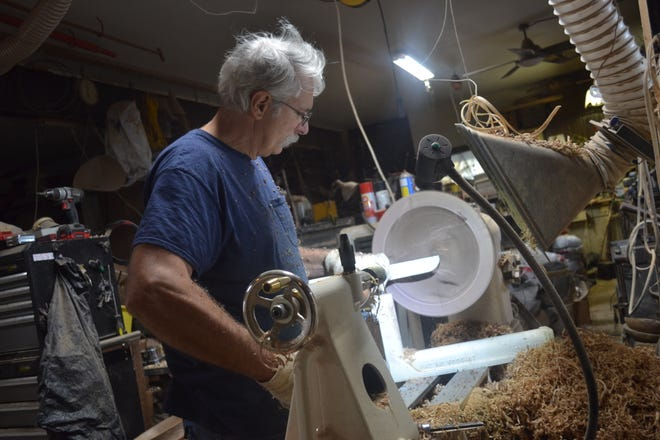 John Fulkert turns a bowl on a lathe in his Port Clinton home. The bowls take up to two years to dry before they can be finished.