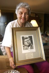 In her Greenville home Friday, Nov. 21, 2003, Lily Johnson holds an autographed photo of John F. Kennedy that he sent to her mother when he was president.