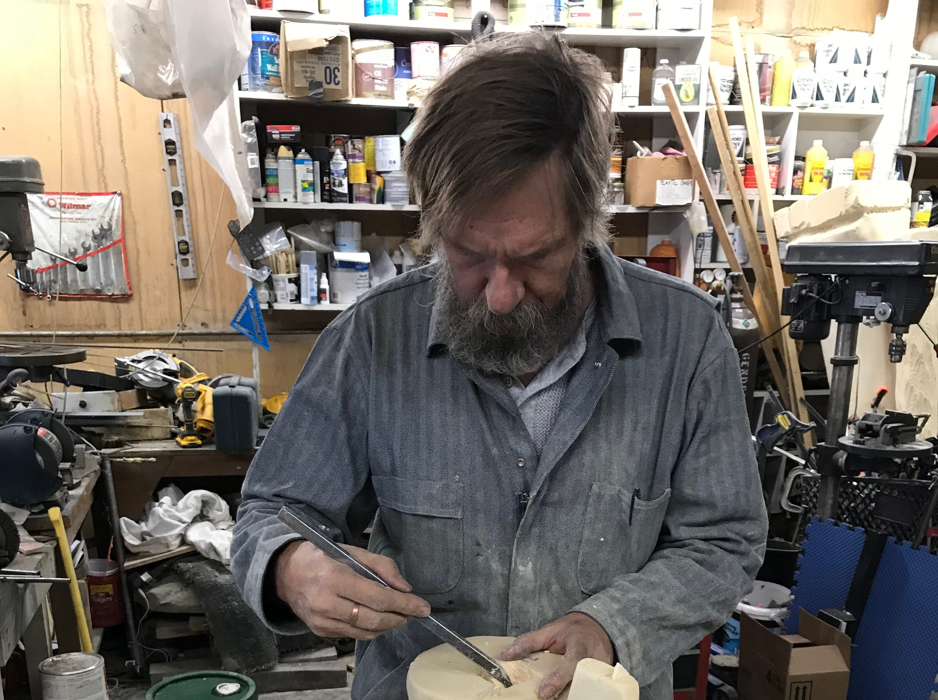 "Tony Lesofski carves a hole in a foam ""fossil"" for a rod to pass through to connect the piece with the rest of the tail. The dinosaur skeleton has taken two years and become Bynum's biggest employer."