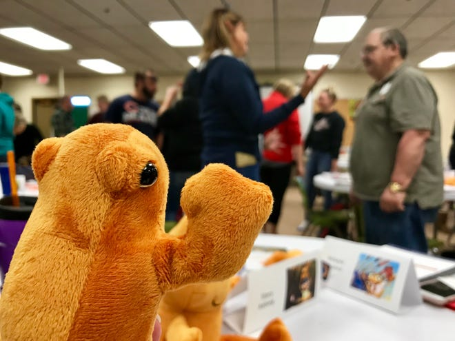 Orange frogs serve as mascots during a happiness training for Conrad School staff. Staff paired up for an exercise on noticing details about each other that turned into a lesson on embracing change.