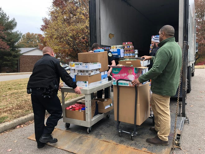 Henderson Police Department officers help load donated food items into a Tri-State Food Bank truck Tuesday.