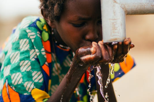 Child sips from a well