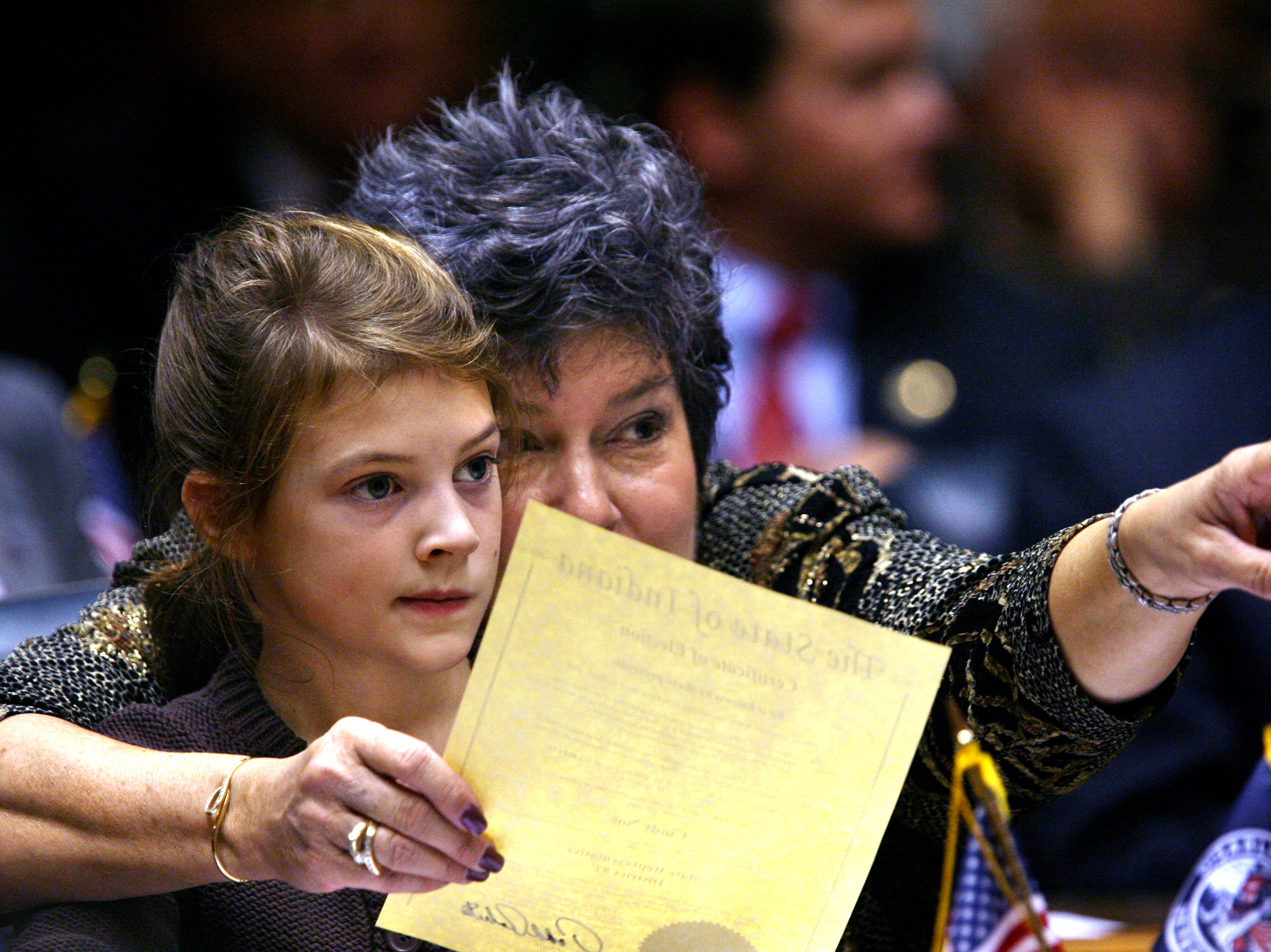 Rep. Cindy Noe, R-Indianapolis, points to the front of the House of Representatives with her granddaughter, Claire Nieshalla, 7, sitting on her lap as the Indiana House begins business on Organization Day at the Statehouse on Tuesday, November 18, 2008. Among the issues legislators are expected to tackle when the next session gets underway in January are the budget, property tax caps and education funding. (Charlie Nye / The Star).