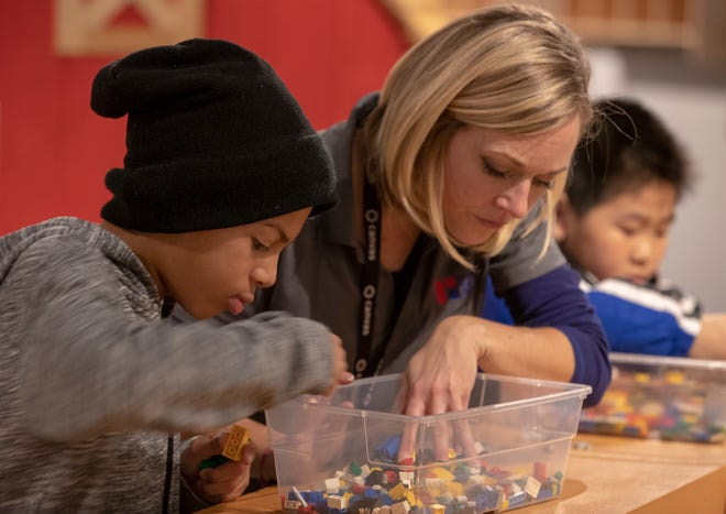 Elijah Sliwa (Ieft), gets a hand with looking for a LEGO piece from Teacher in Residence Amy Murch at Conner Prairie, Fishers, Monday, Nov. 19, 2018. The learning lab lets local fourth graders study new things at the immersive facilities at the living history museum which has promoted Science, Technology, Engineering and Math fields in recent years.