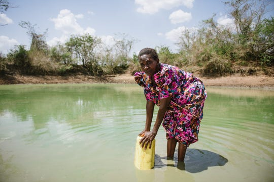 A woman who lacks access to clean drinking water collects water from a standing pool.