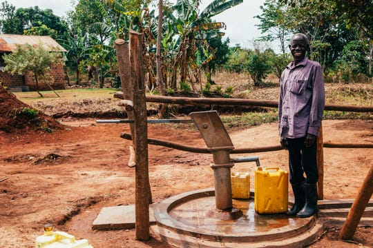 A man fills jugs from a water well built by Thirst Project.
