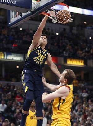 Indiana Pacers forward Doug McDermott (20) slams down two points on Utah Jazz forward Joe Ingles (2)  in the first half of their game on Monday, Nov. 19, 2018.