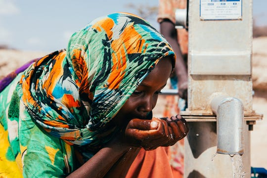 A child drinks from a well that was installed by Thirst Project to provide a community with safe drinking water.